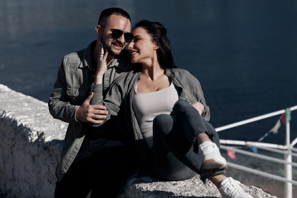 un homme et une femme assis sur le dos s'embrassent en riant