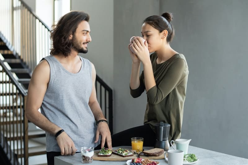 un homme et une femme dans la cuisine buvant du café