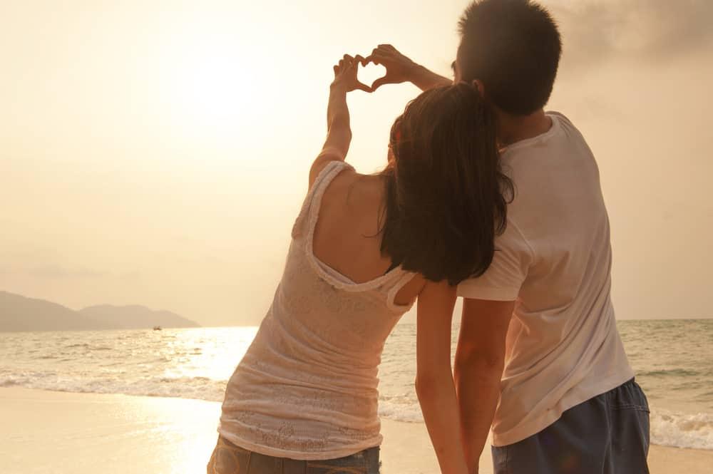 un homme et une femme debout près de la plage, le dos tourné, le cœur droit avec les mains