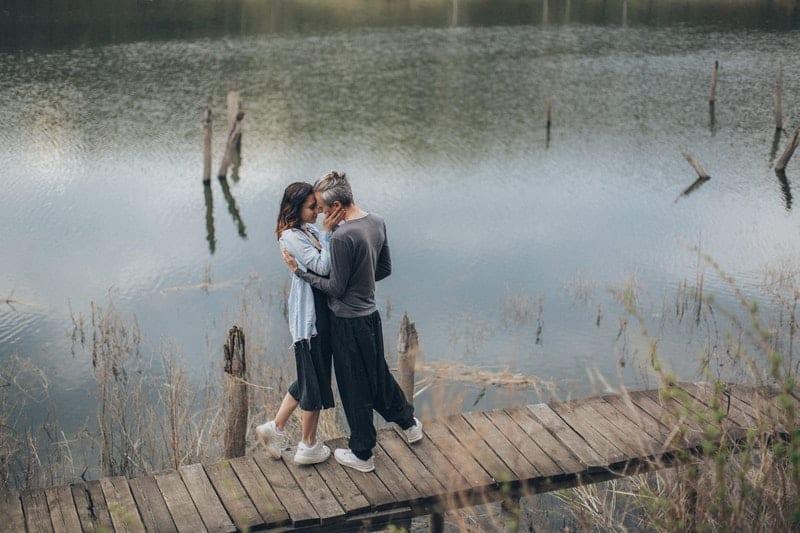 un homme et une femme embrassant à côté de la jetée
