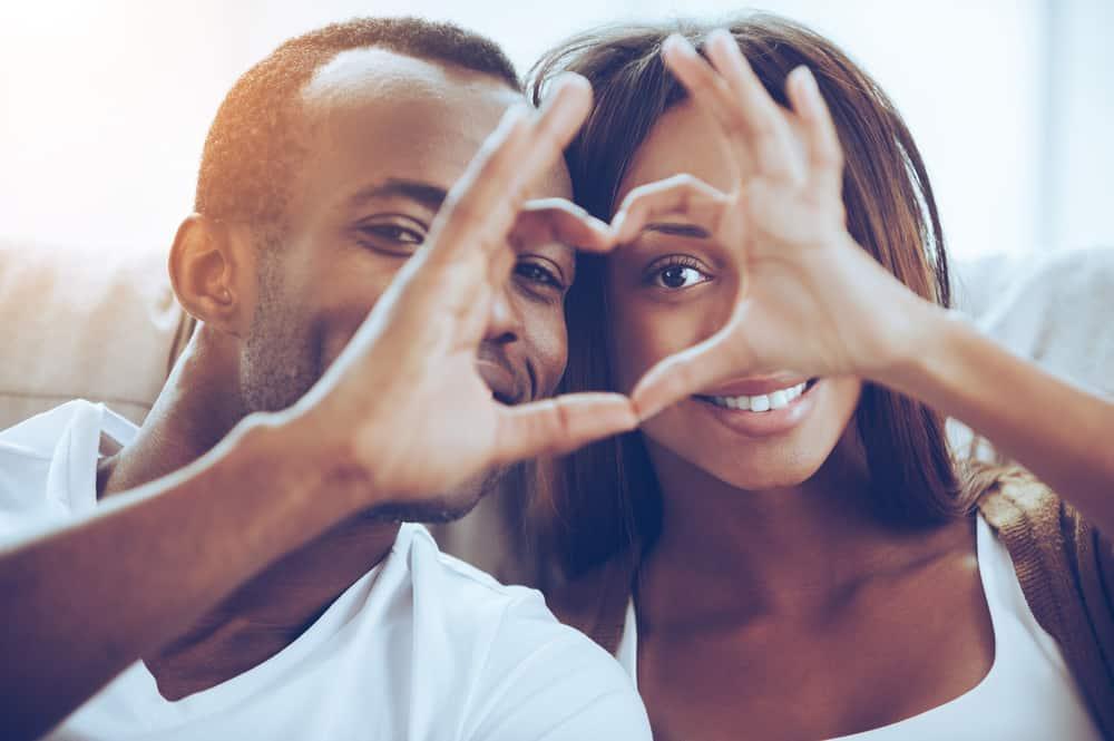 un homme et une femme ont fait un cœur avec leurs mains