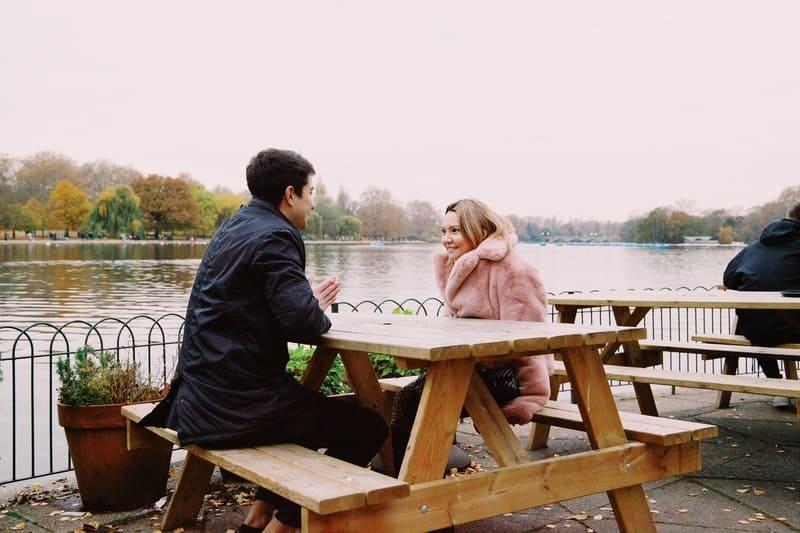 un homme et une femme parlent à table