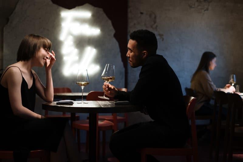 un homme et une femme s'assoient à une table et boivent du vin