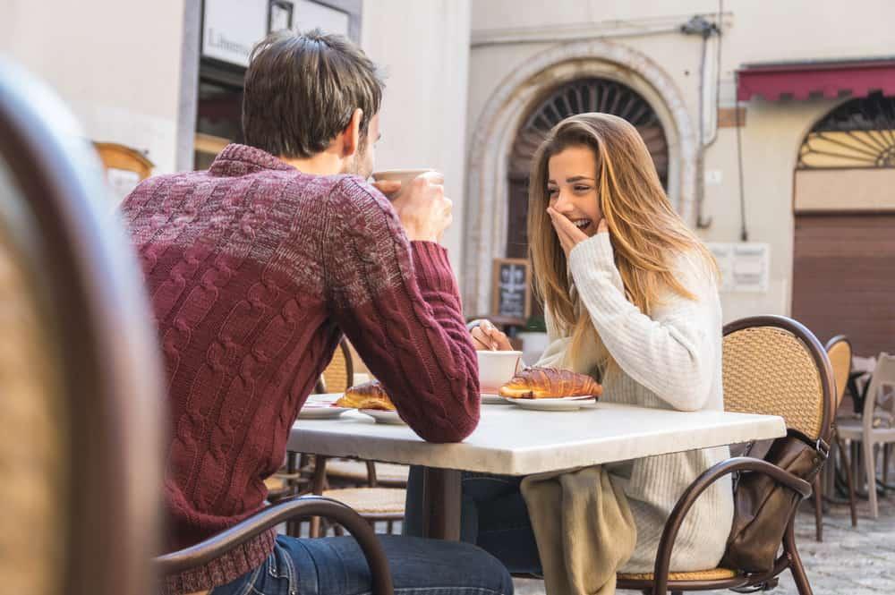 un homme et une femme s'assoient à une table et rient