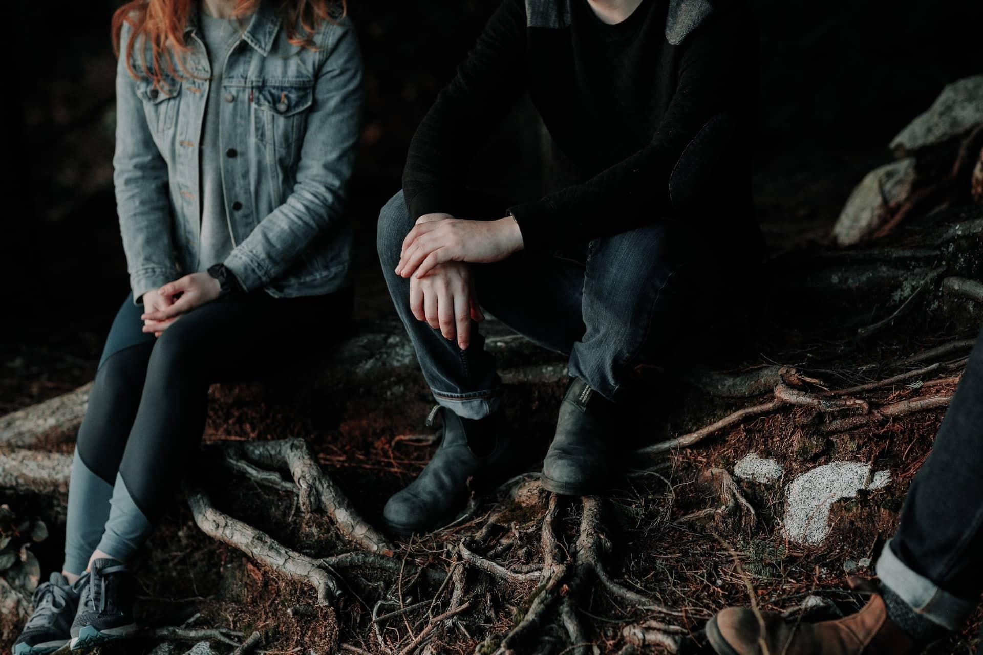 un homme et une femme s'assoient et parlent dans les bois