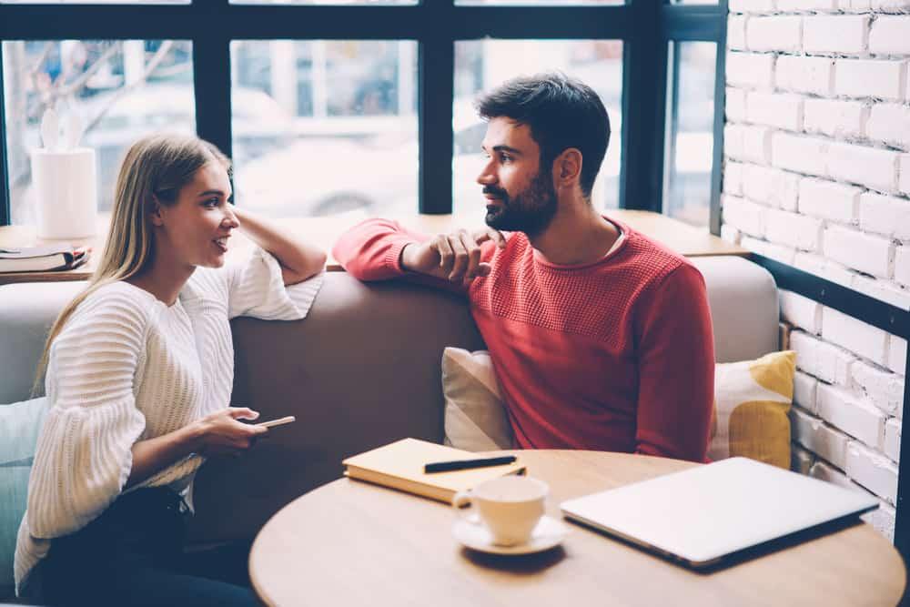un homme et une femme s'assoient longtemps l'un à côté de l'autre et se regardent pendant qu'ils parlent