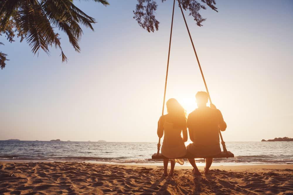 un homme et une femme sont assis ns se balançant au bord de la mer