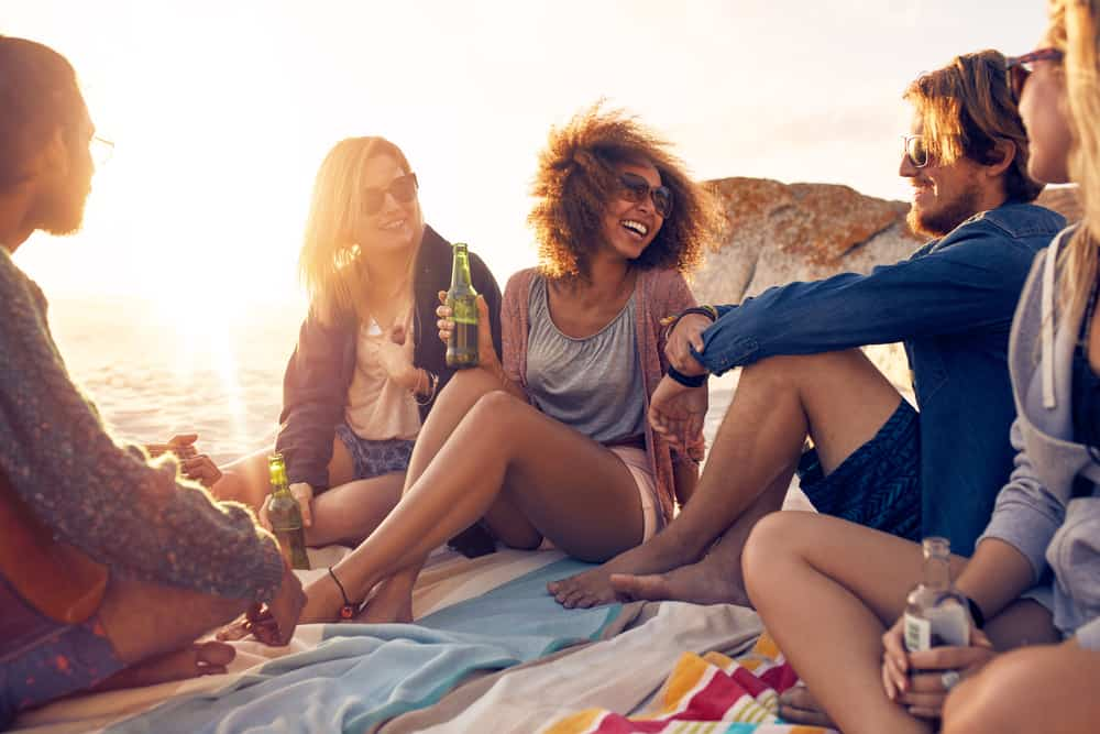 un homme et une femme sont assis sur la plage avec des amis et rient
