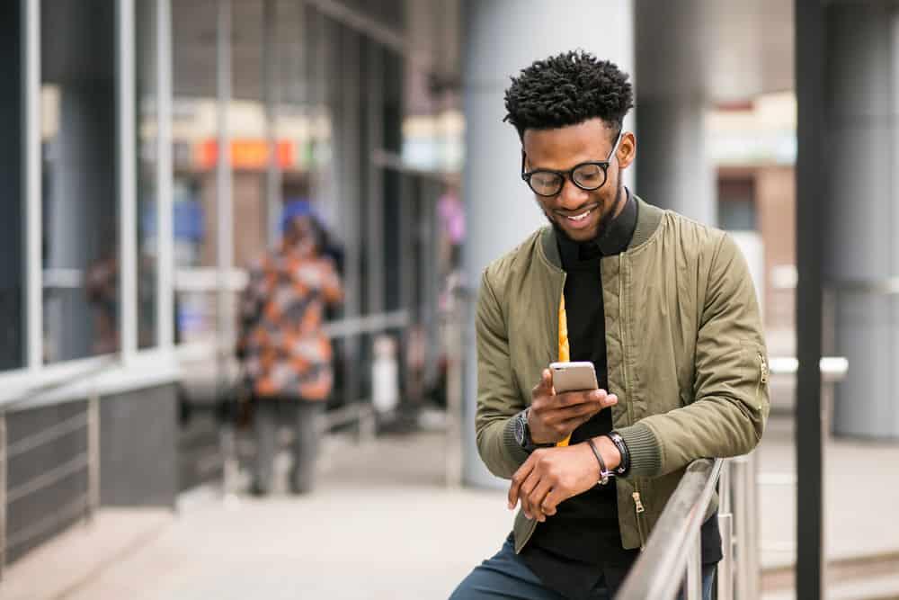 un homme noir se tient près de la clôture et envoie des SMS