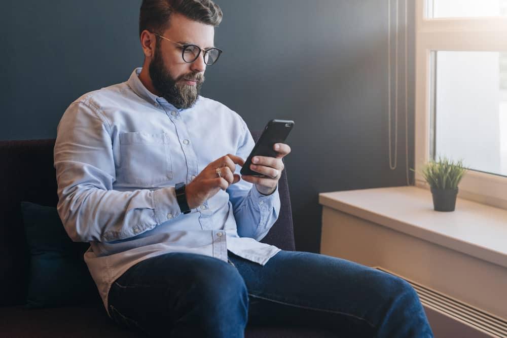 un homme sérieux est assis dans un fauteuil et envoie des SMS