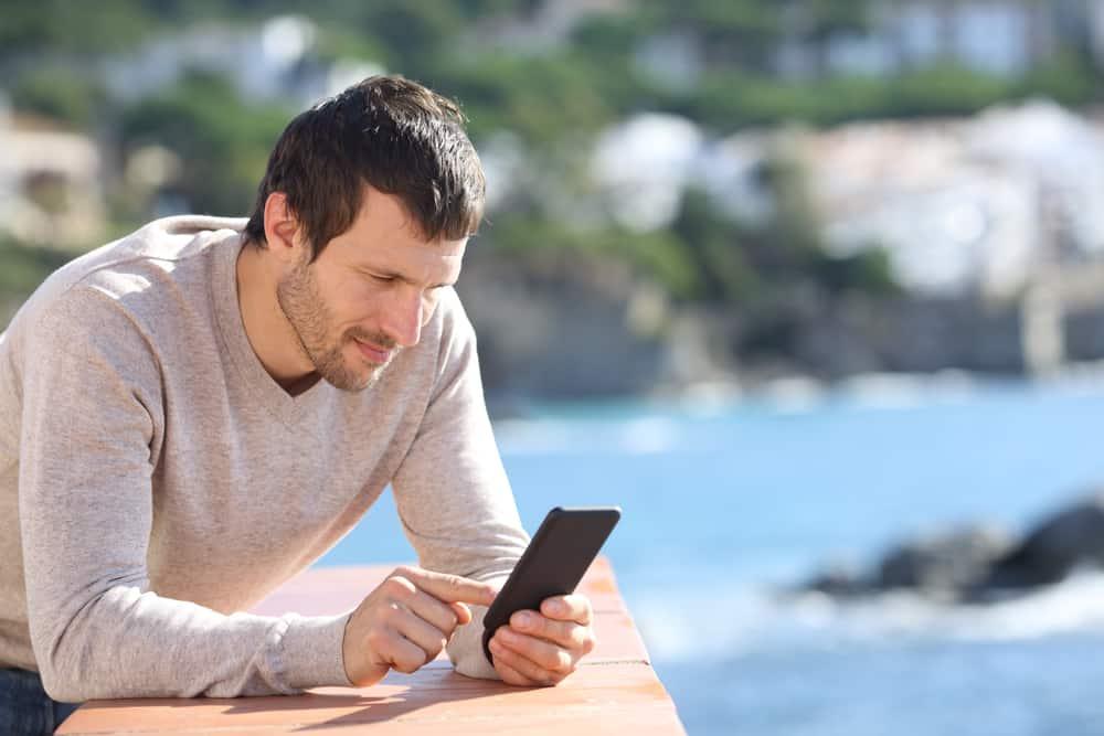 un homme sérieux sur la terrasse est debout et envoie des SMS