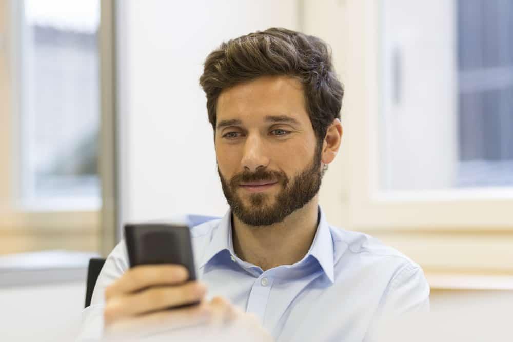 un homme souriant avec une barbe est assis et écrit un sms