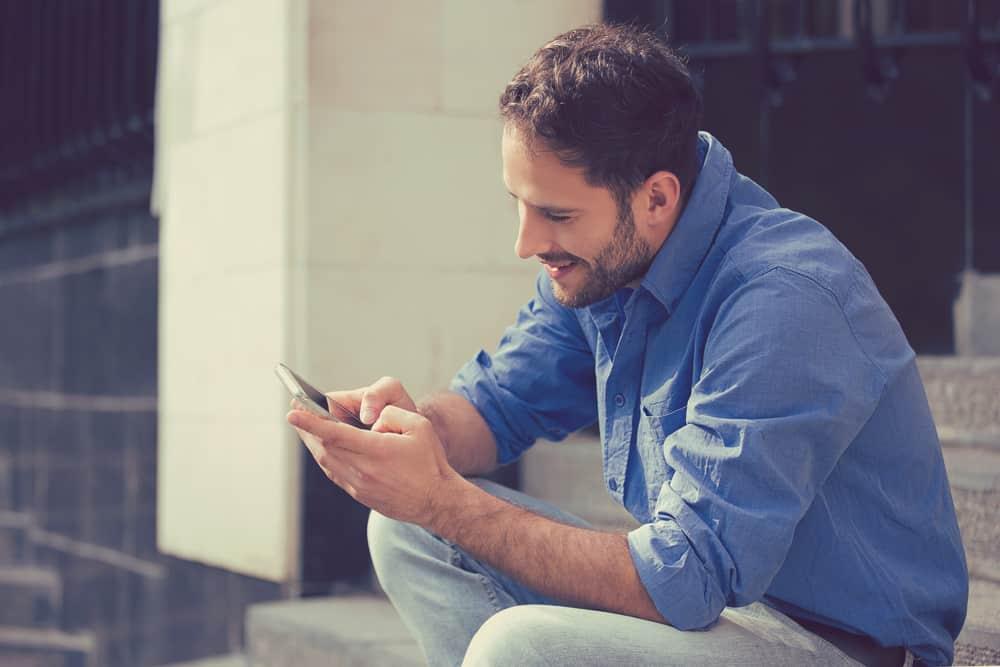 un homme souriant dans une chemise bleue est assis dehors dans les escaliers et envoie des SMS