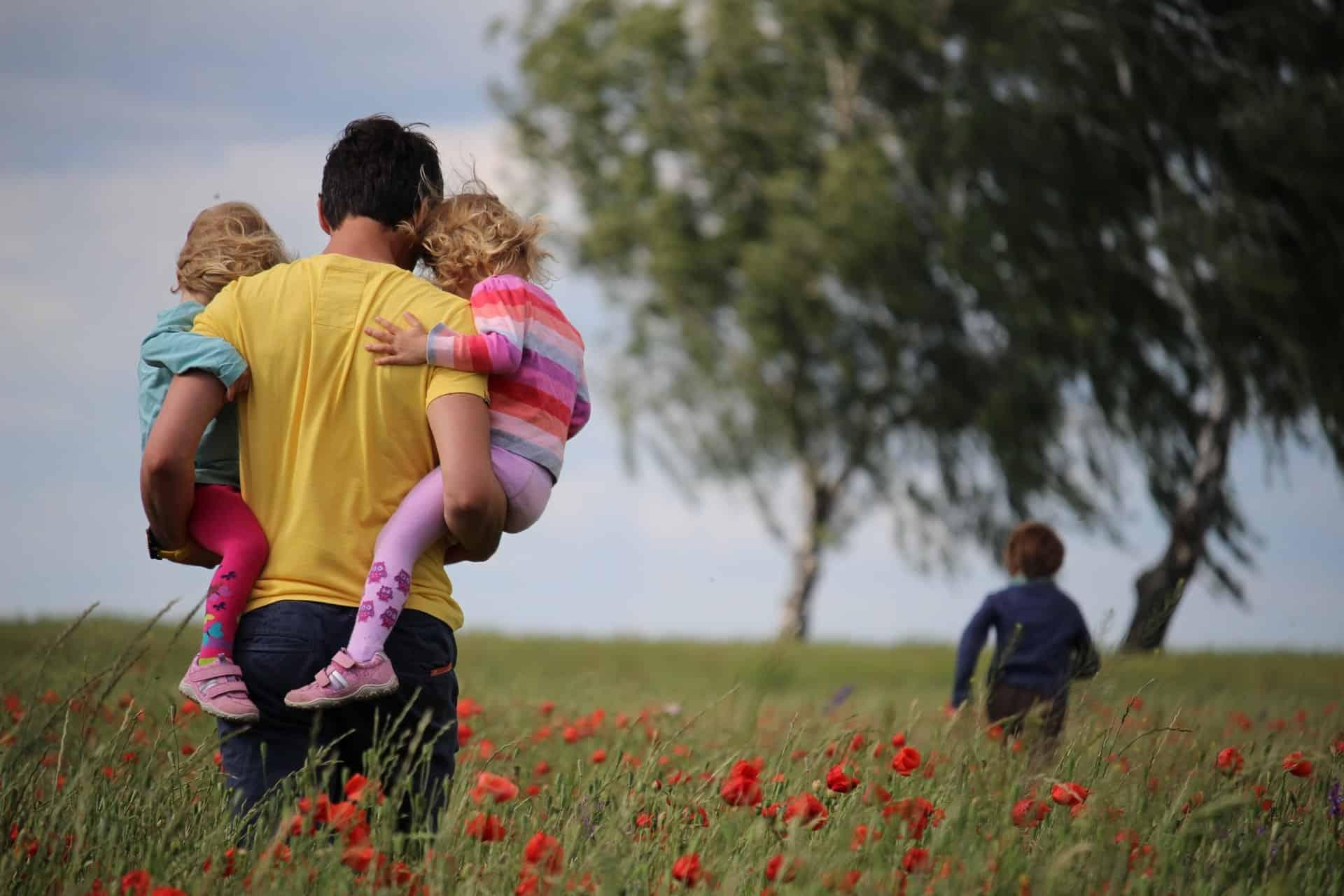 un homme transporte des enfants à travers le champ