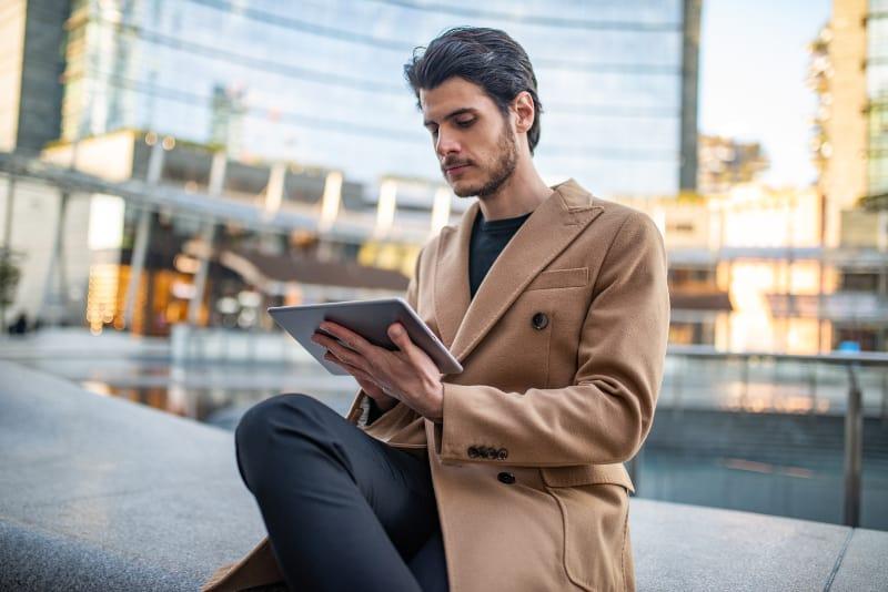 un homme utilise un ordinateur portable assis devant un immeuble