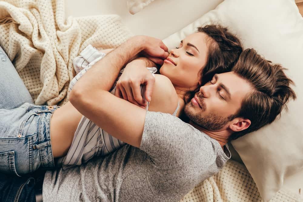 un jeune couple amoureux dort dans une étreinte