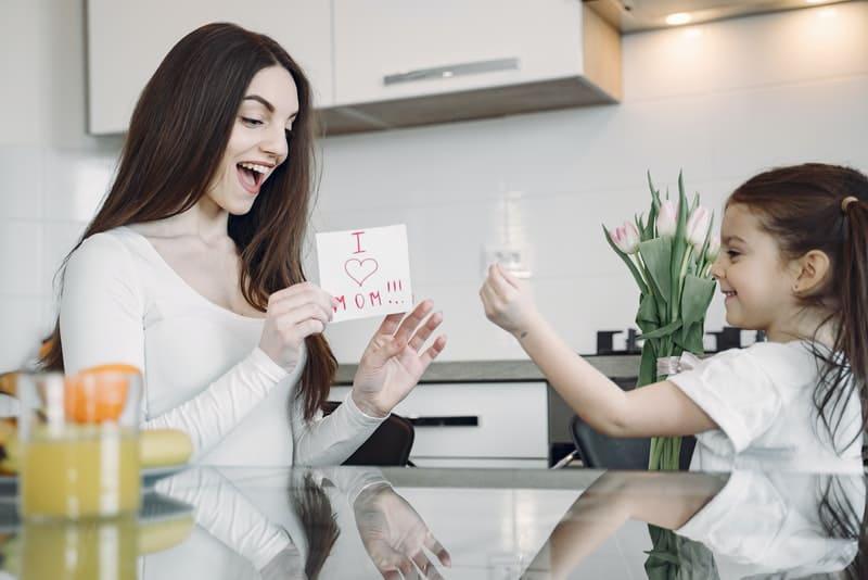 une baby-sitter joue avec un enfant dans la cuisine