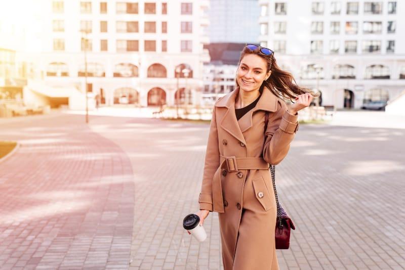 une belle jeune fille dans un manteau se promène dans la ville