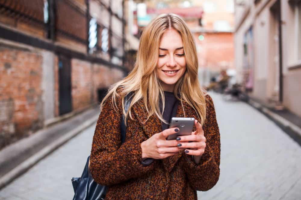 une blonde souriante se tient dans la rue et écrit un sms