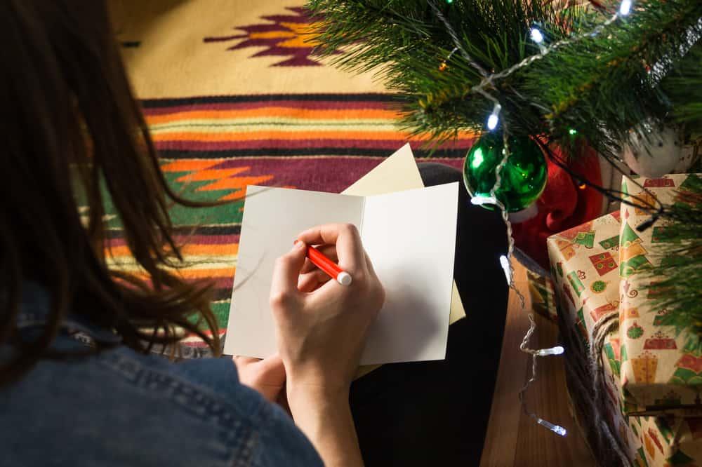 une femme à côté d'un pin écrit une carte de vœux