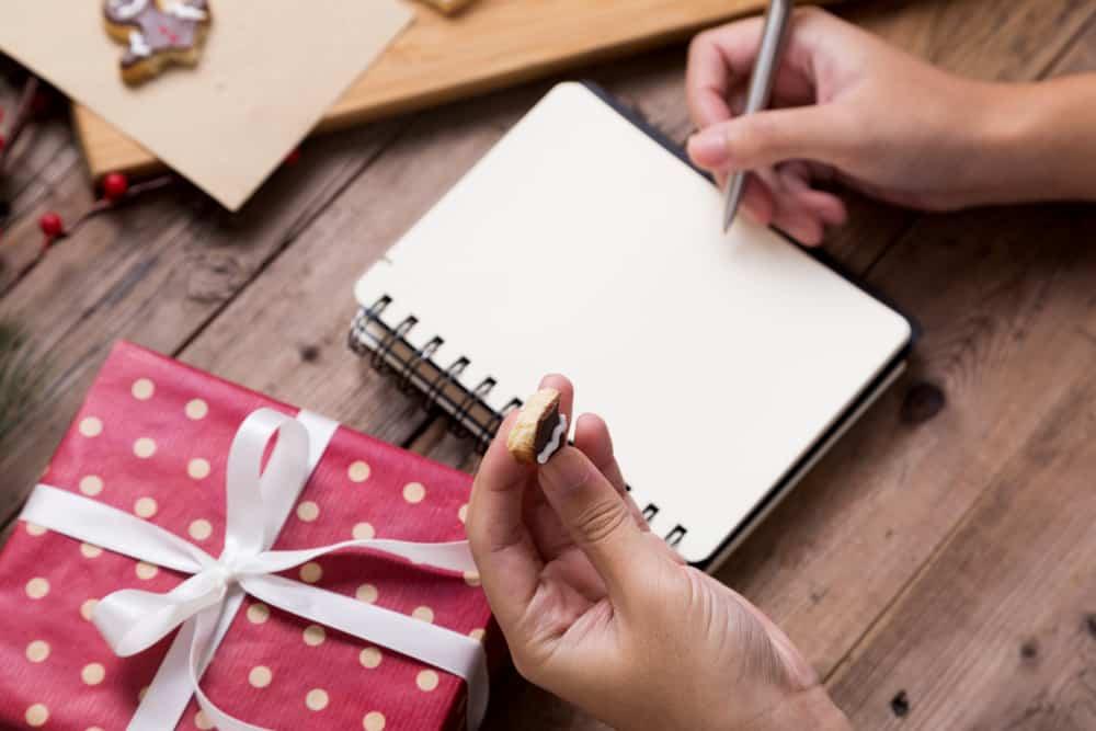 une femme assise, manger un cookie et écrire une carte de voeux