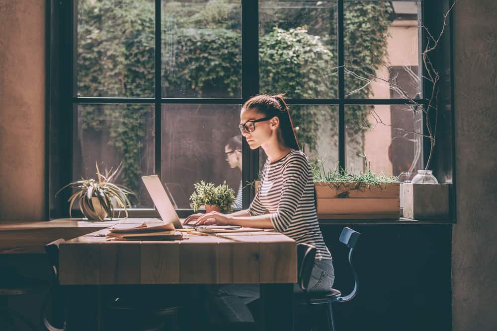 une femme aux cheveux attachés assis à un bureau et travaillant sur un ordinateur portable