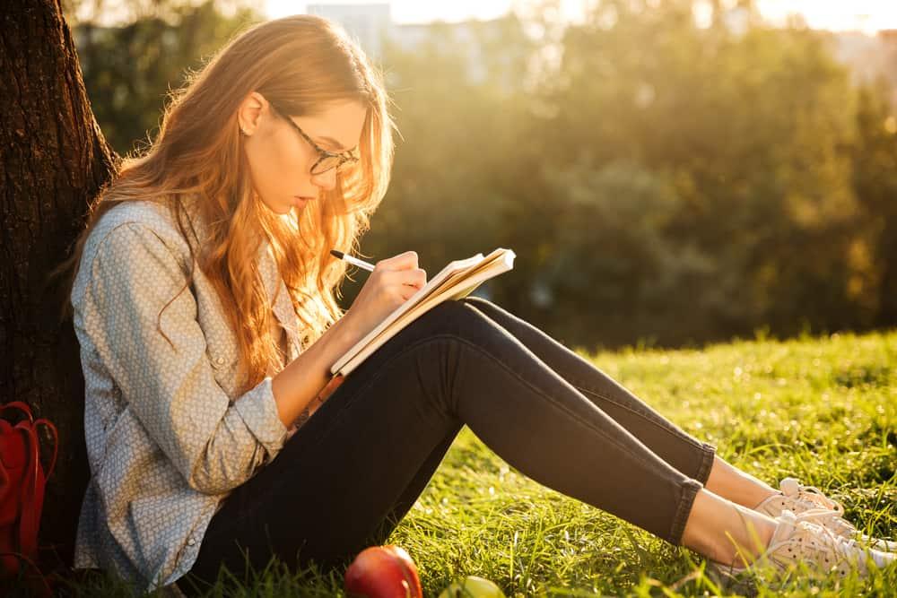 une femme aux cheveux blonds est assise sur l'herbe appuyée contre un arbre et écrit