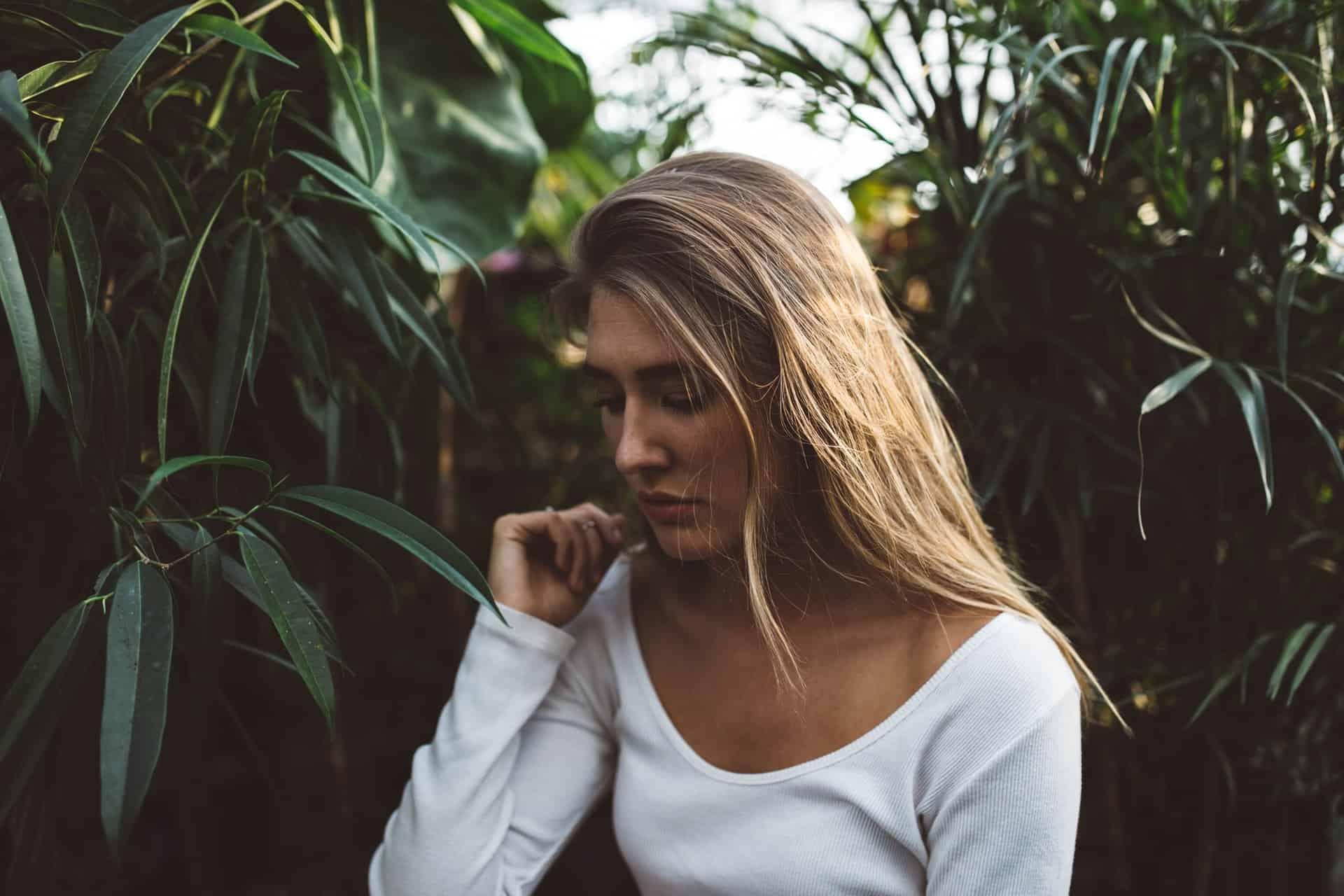 une femme aux cheveux blonds se tient à côté d'un saule