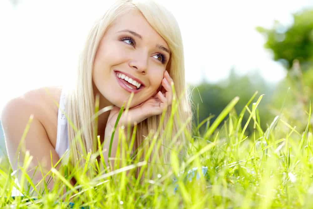 une femme aux cheveux blonds se trouve dans l'herbe et rit