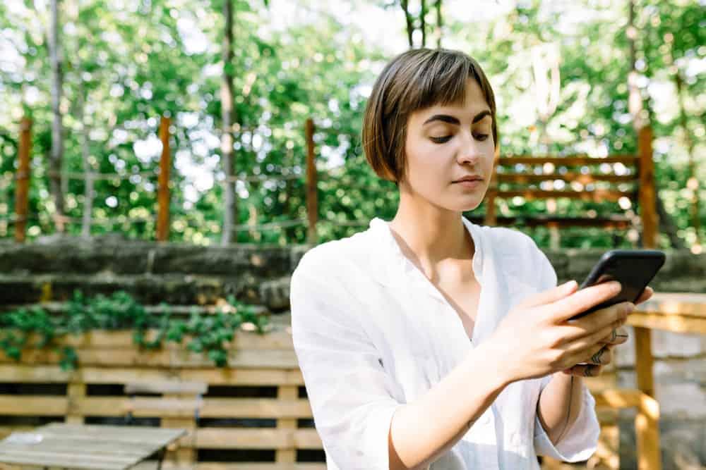 une femme aux cheveux courts se tient dehors et utilise un téléphone portable
