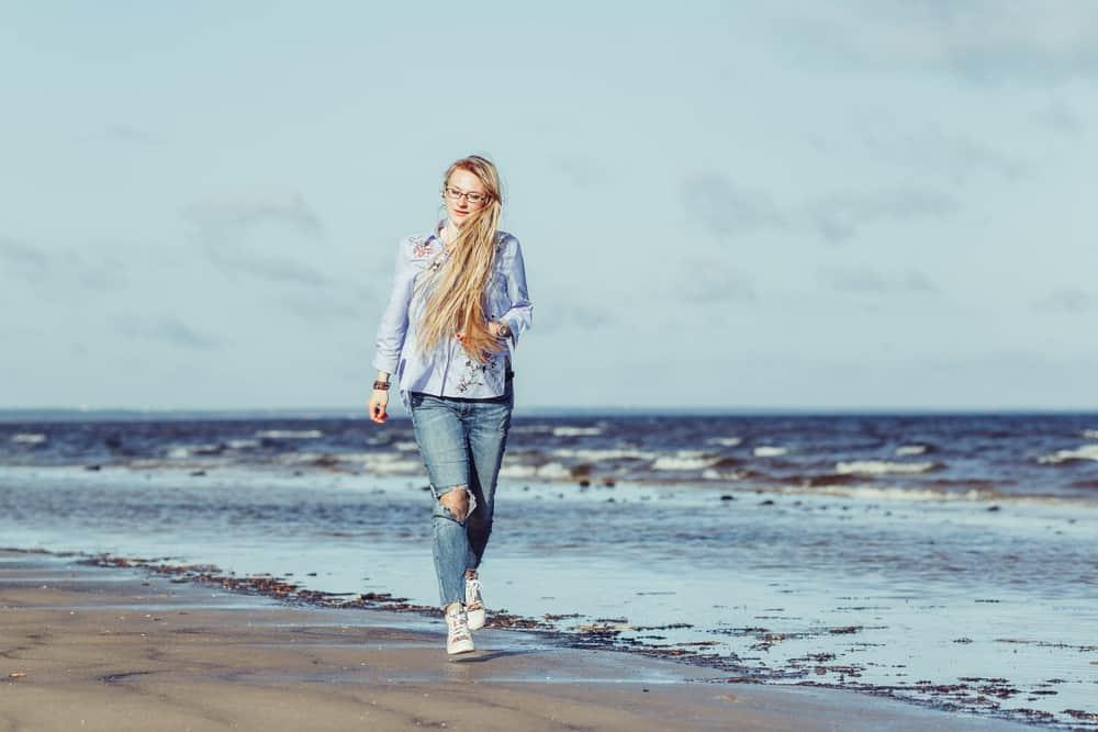 une femme aux longs cheveux blonds définit la plage