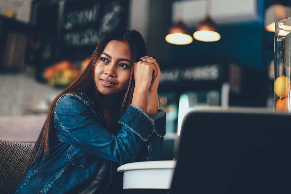 une femme aux longs cheveux noirs est assise seule à une table