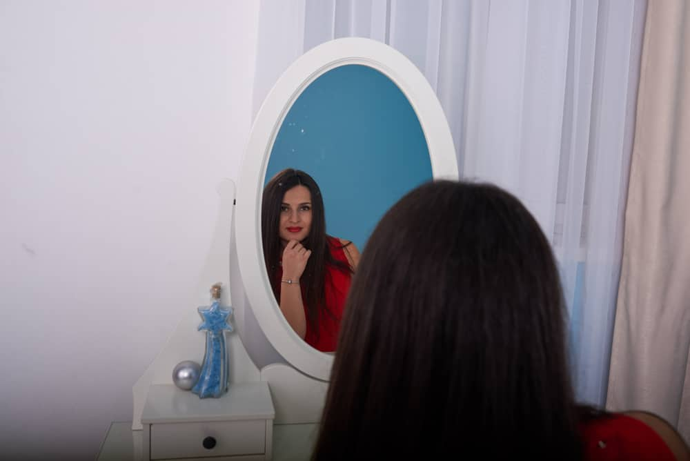 une femme aux longs cheveux noirs se tient devant un miroir de maquillage
