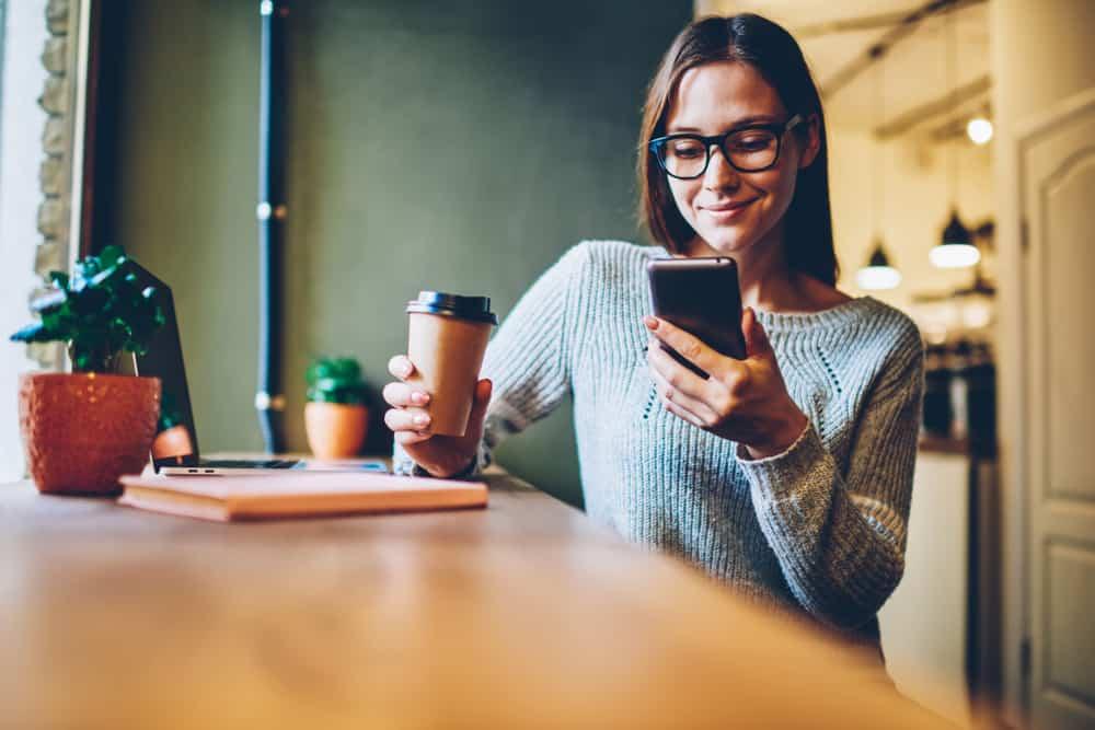 une femme avec des lunettes avec du café lit quelque chose sur son téléphone portable