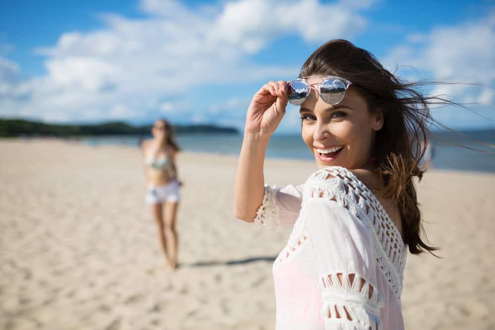 une femme avec des lunettes sur la plage rit
