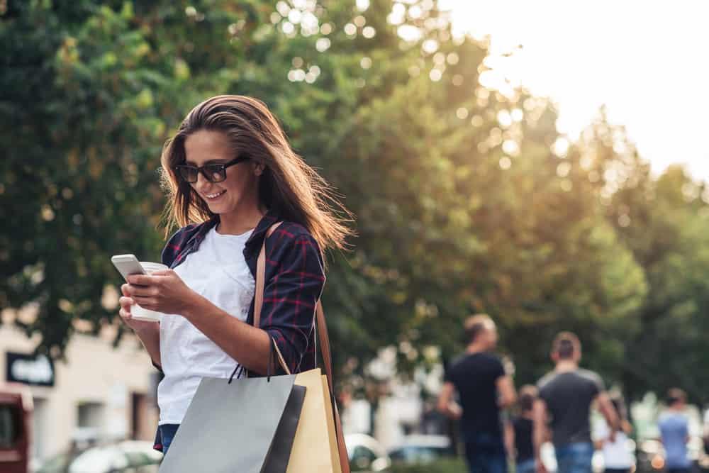 une femme avec des sacs marche dans la rue et un bouton sur le téléphone