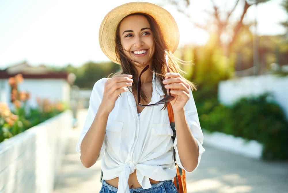 une femme avec un chapeau sur la tête et des lunettes à la main rit