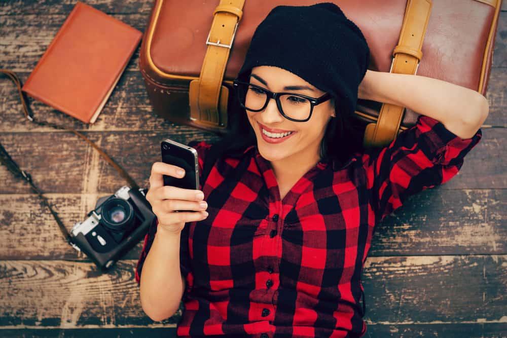 une femme avec un chapeau sur la tête rit et lit des sms