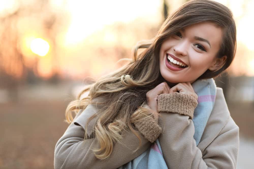 une femme avec un manteau et de la graisse autour du cou rit