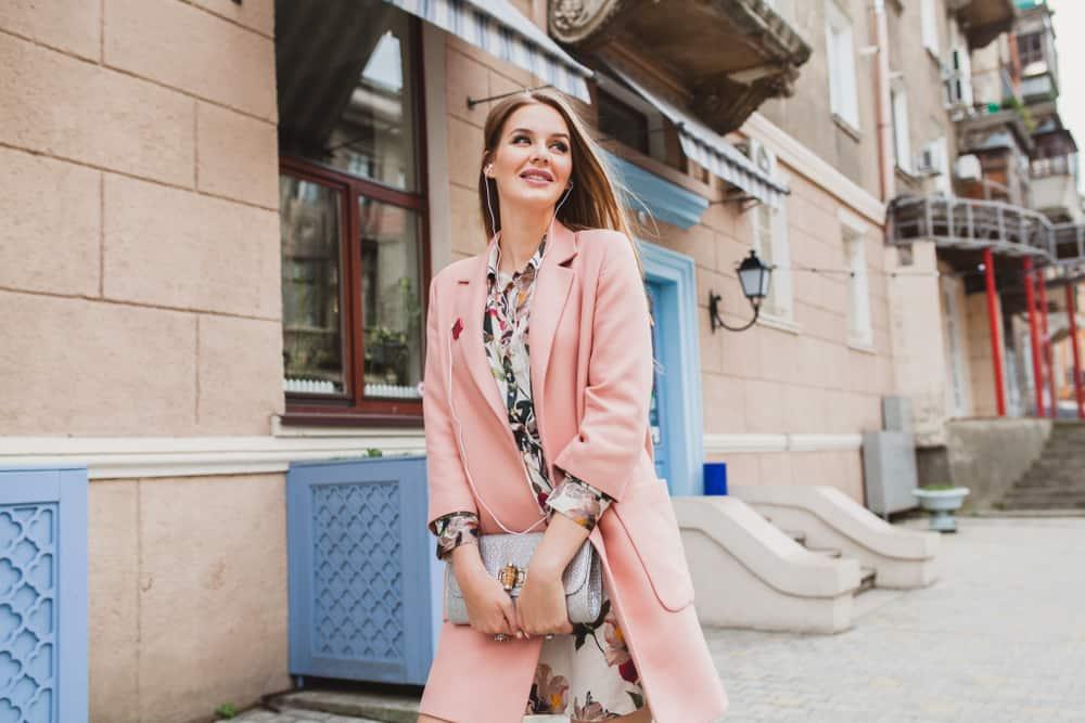 une femme avec un manteau rose marche dans la rue