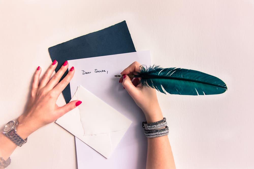 une femme avec un stylo écrit une carte de voeux