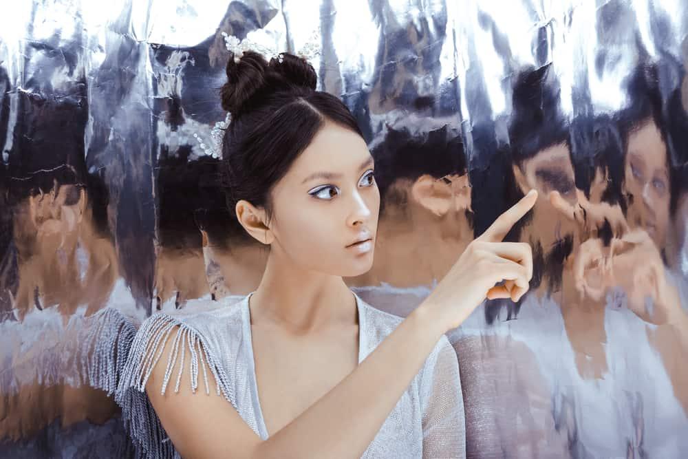 une femme avec une livre sur la tête se regarde dans le miroir