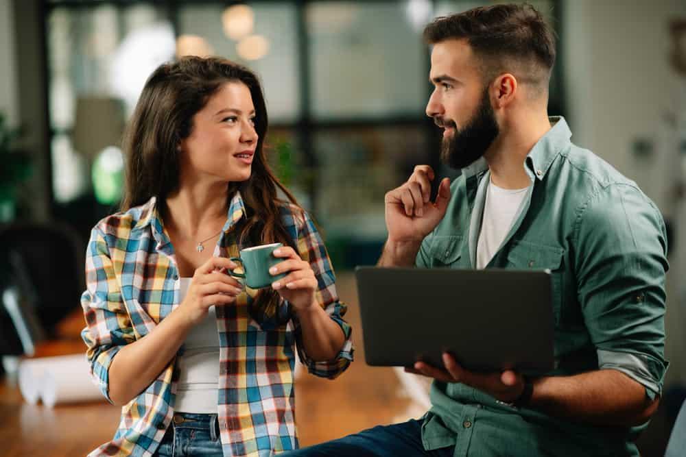une femme avec une tasse de café est debout à côté d'un homme