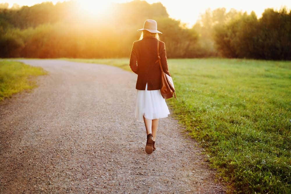 une femme bien habillée avec un chapeau marche dans la rue