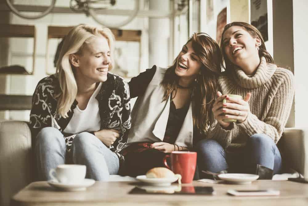 une femme buvant du café avec des amis et riant