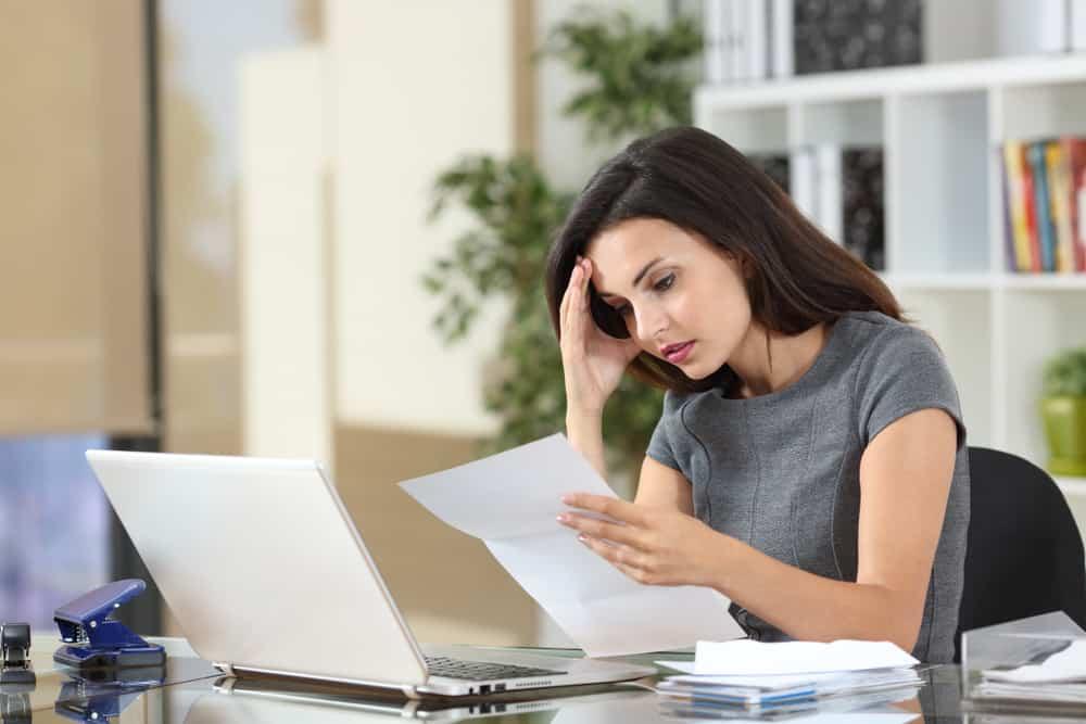 une femme confuse au travail est assise derrière un ordinateur portable