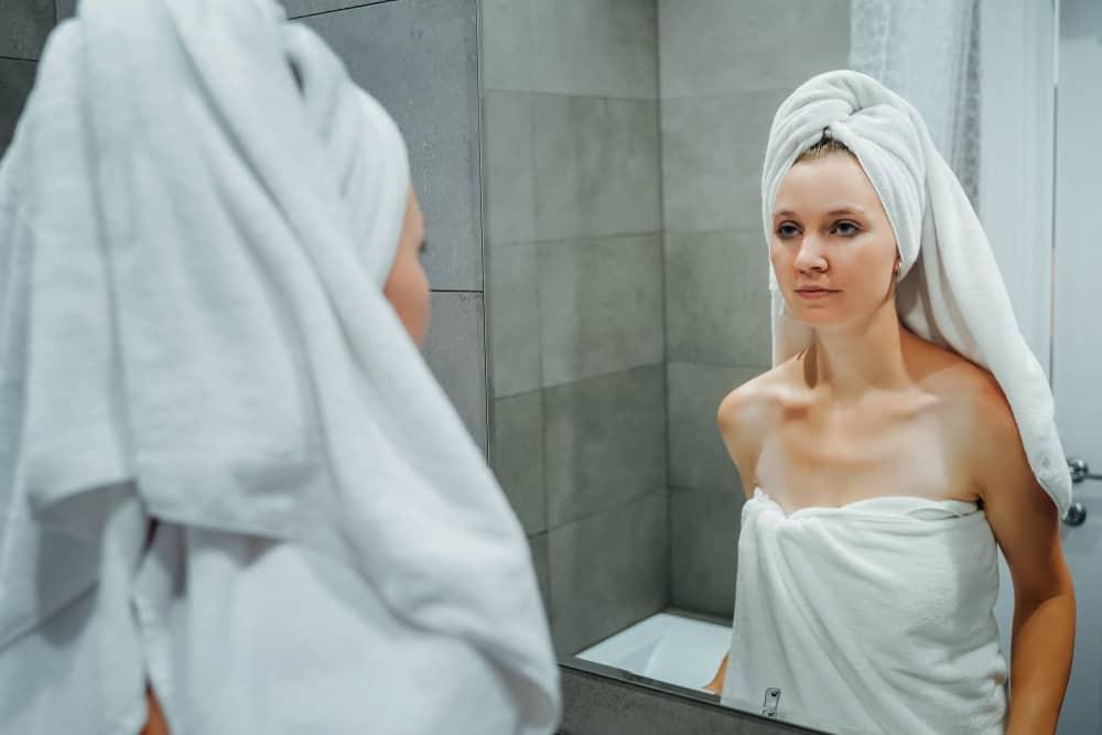 une femme déçue se regarde dans le miroir