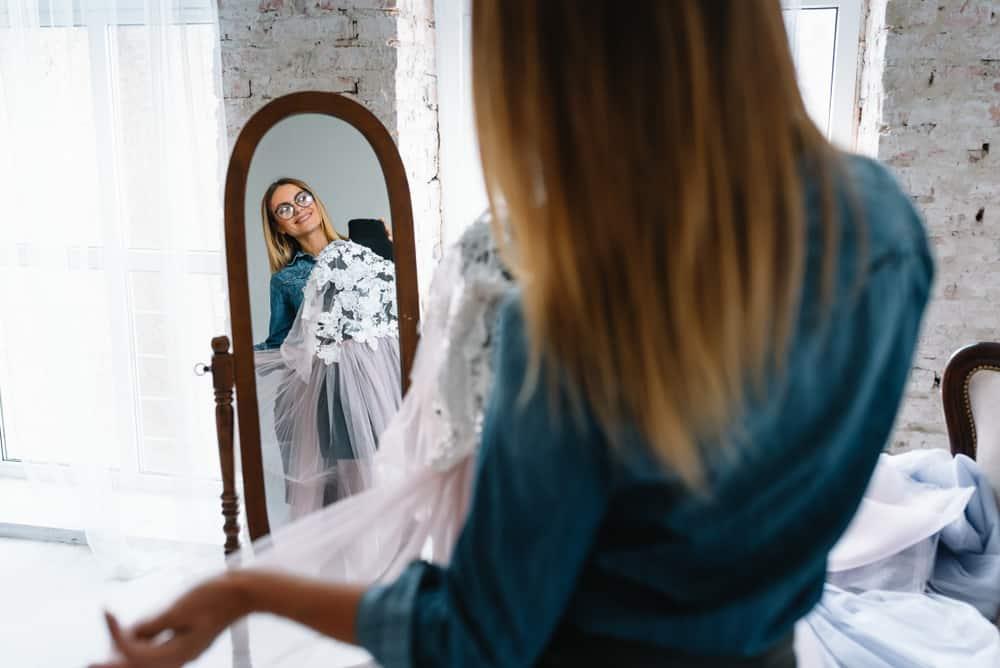 une femme debout devant un miroir avec une robe dans ses mains