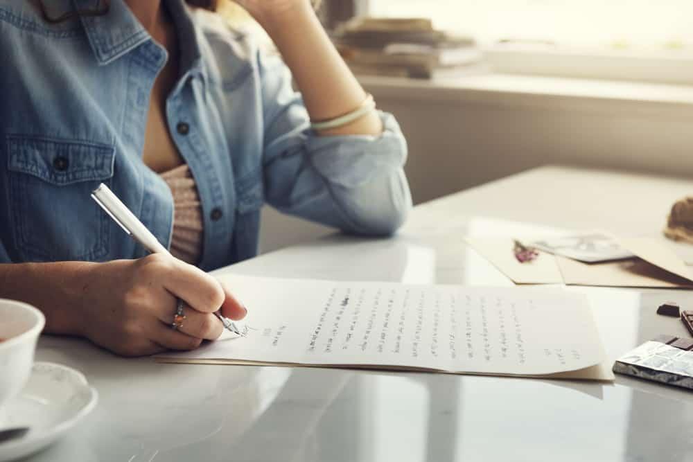 une femme en chemise en jean écrit une lettre