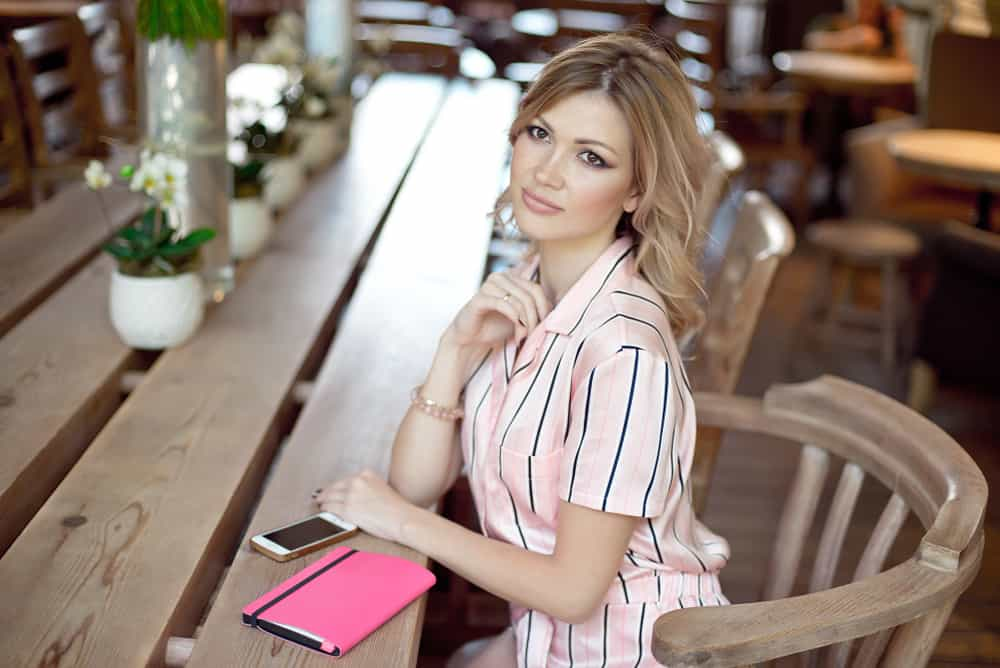 une femme est assise à une table à côté de son téléphone et de son agenda